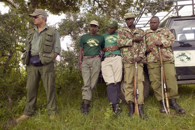 El Dr. Karmari, un veterinario y funcionamiento del grupo para encontrar trampas el capturar de animales en el parque nacional de imagen de archivo libre de regalías