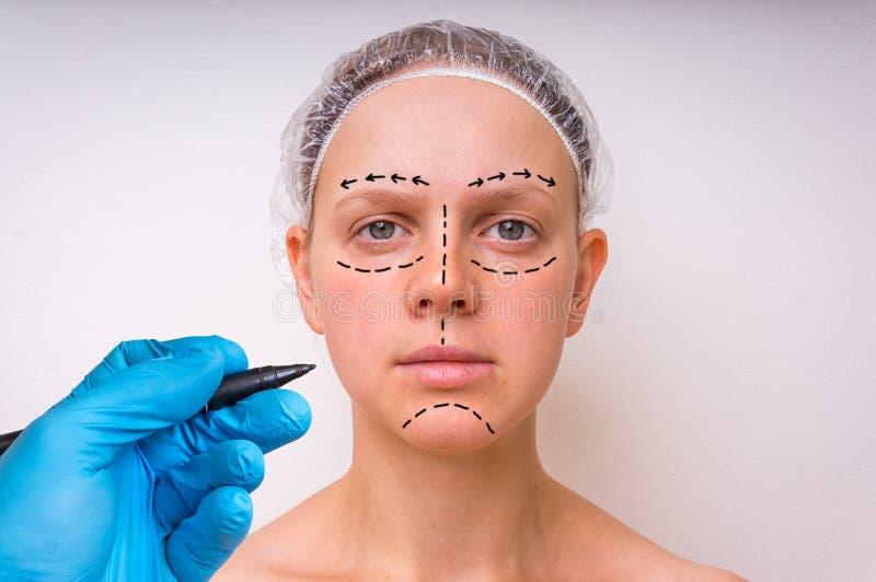 El drenaje del doctor de la cirugía plástica alinea con el marcador en cara paciente imagen de archivo
