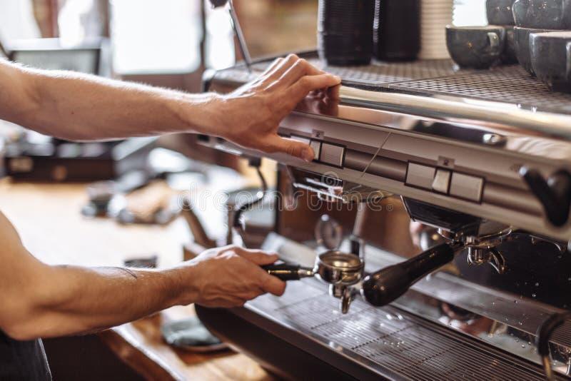 El dueño de cafetería está girando la cafetera imagenes de archivo