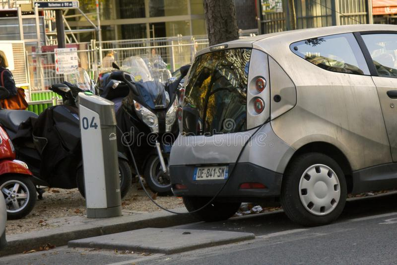 El dueño parisiense recarga las baterías de su coche eléctrico en la estación de carga fotos de archivo