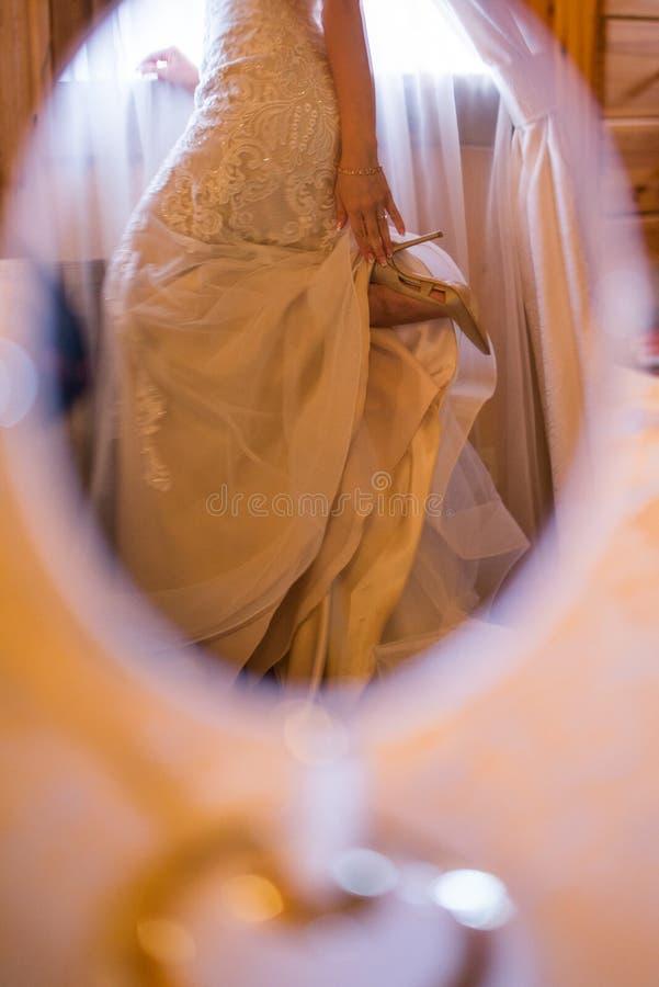 El duplicar: la novia en el vestido de boda guarda el talón de sus zapatos fotografía de archivo libre de regalías