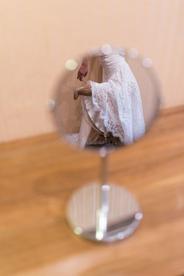 El duplicar: la novia en el vestido de boda guarda el talón de sus zapatos imagenes de archivo