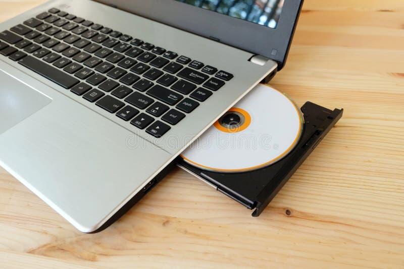 El DVD del CD conduce al escritor Burner Reader interno del ordenador portátil en de madera foto de archivo