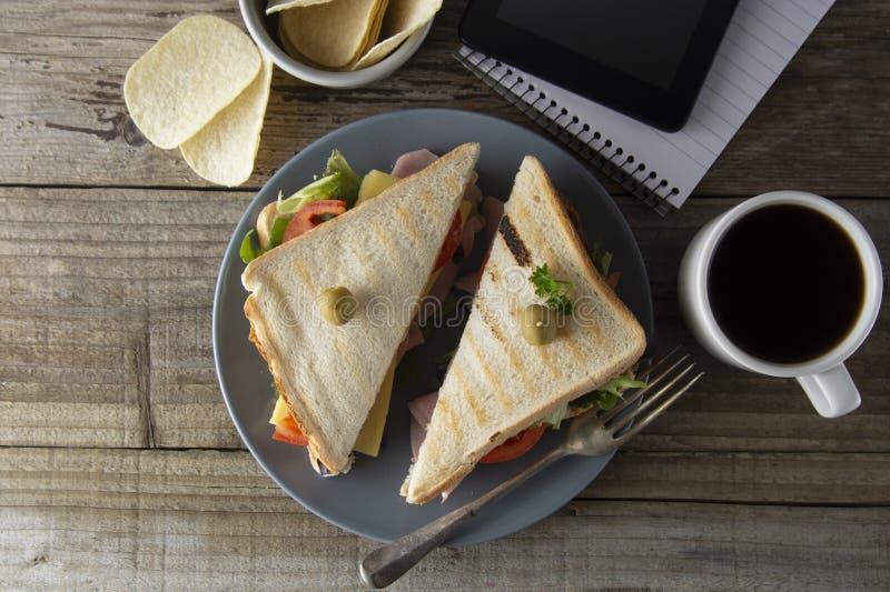 El eatting malsano en el lugar de trabajo Triángulo, bocadillo de club con el jamón y verduras Tableta, pantalla del artilugio  imagen de archivo libre de regalías