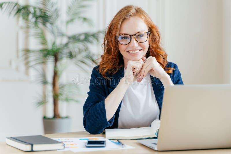 El economista de sexo femenino satisfecho del haird rojo alegre desarrolla proyecto de inicio financiero, presenta en interior de fotos de archivo