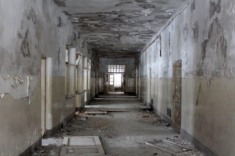 El edificio abandonado dilapidó pasillo con las puertas y las ventanas quebradas foto de archivo libre de regalías