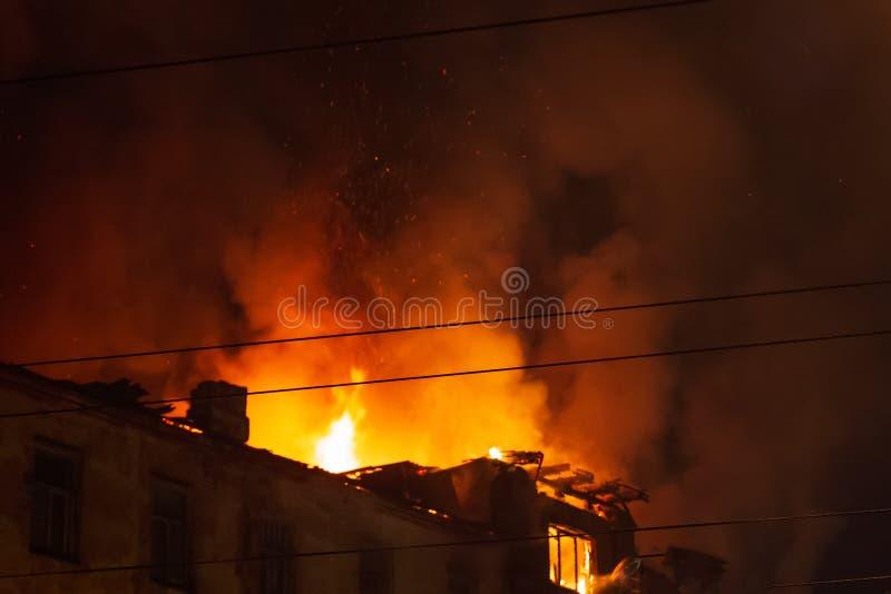 El edificio ardiente en la noche, tejado de la casa en fuego flamea imagenes de archivo