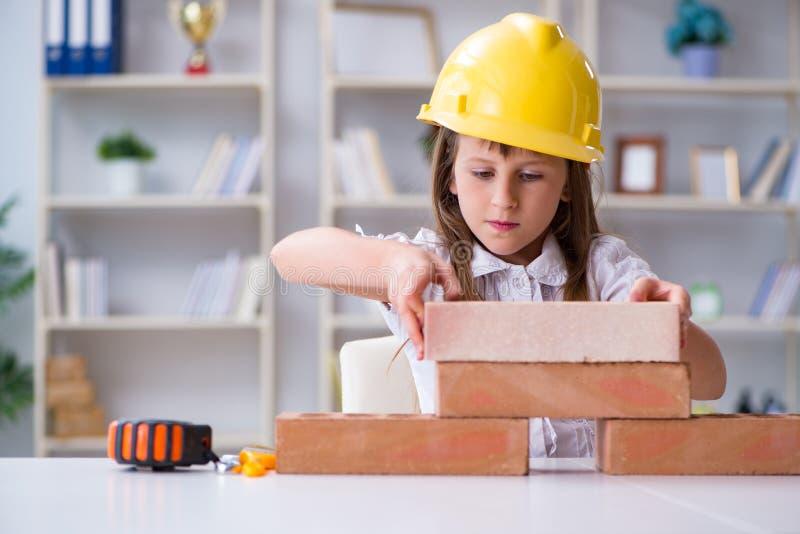 El edificio de la chica joven con los ladrillos de la construcción imagenes de archivo