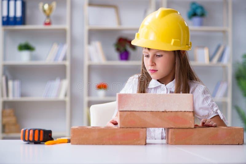 El edificio de la chica joven con los ladrillos de la construcción fotos de archivo libres de regalías