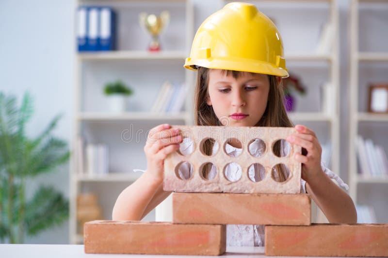 El edificio de la chica joven con los ladrillos de la construcción imágenes de archivo libres de regalías