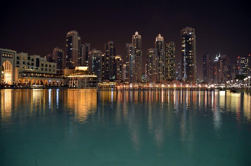 El edificio de la ciudad en la noche y el agua reflejan la foto imagenes de archivo