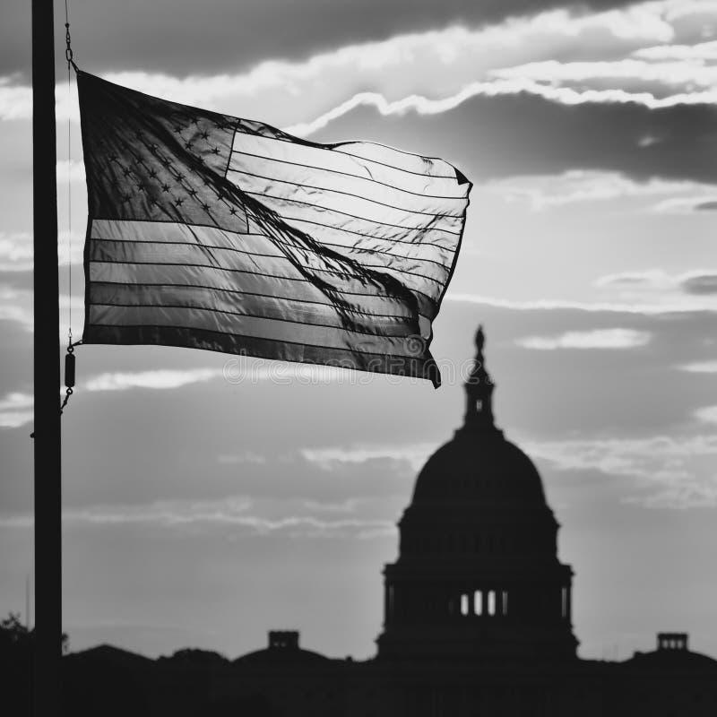 El edificio del capitolio de Estados Unidos y los E.E.U.U. señalan la silueta por medio de una bandera en la salida del sol, Washi fotos de archivo
