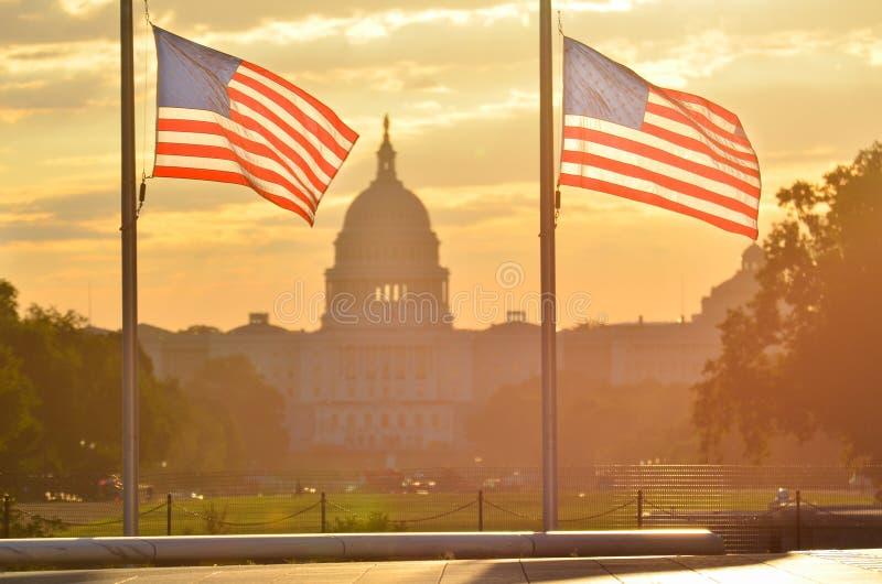 El edificio del capitolio de Estados Unidos y los E.E.U.U. señalan la silueta por medio de una bandera en la salida del sol, Washi imagen de archivo