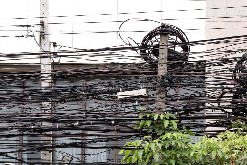 El edificio del frente del enredo del cable eléctrico y el arbusto de alto voltaje del árbol, peligro de la energía eléctrica del fotos de archivo