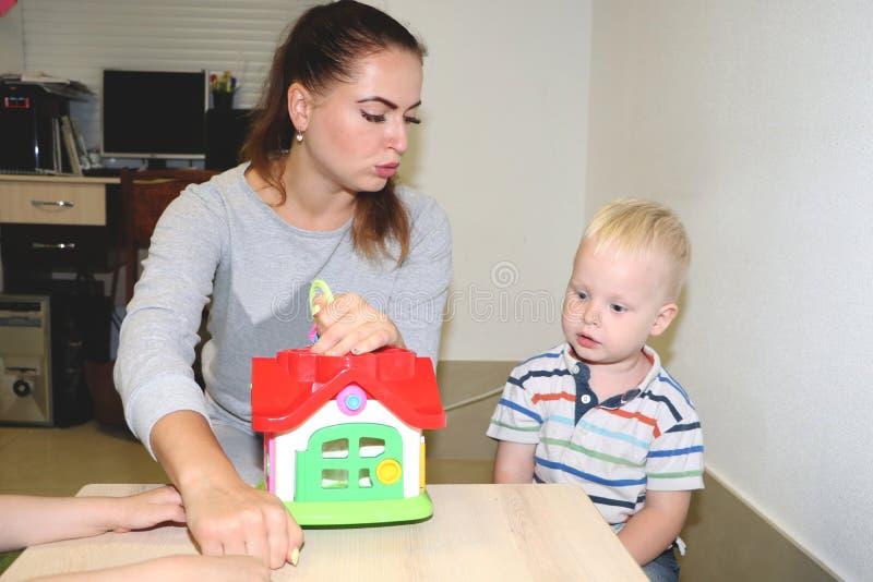 El educador trata del niño en la guardería Creatividad y desarrollo del niño foto de archivo