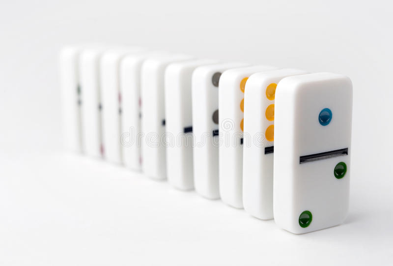 El efecto de dominó de los bloques blancos, con números coloridos Foco selectivo en la parte delantera de los bloques del dominó imagenes de archivo