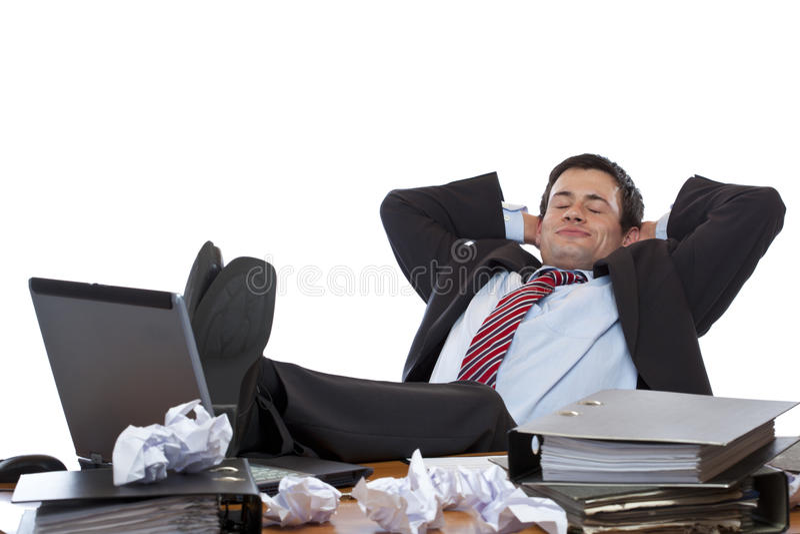 El ejecutivo joven se relaja con los pies en el escritorio imágenes de archivo libres de regalías