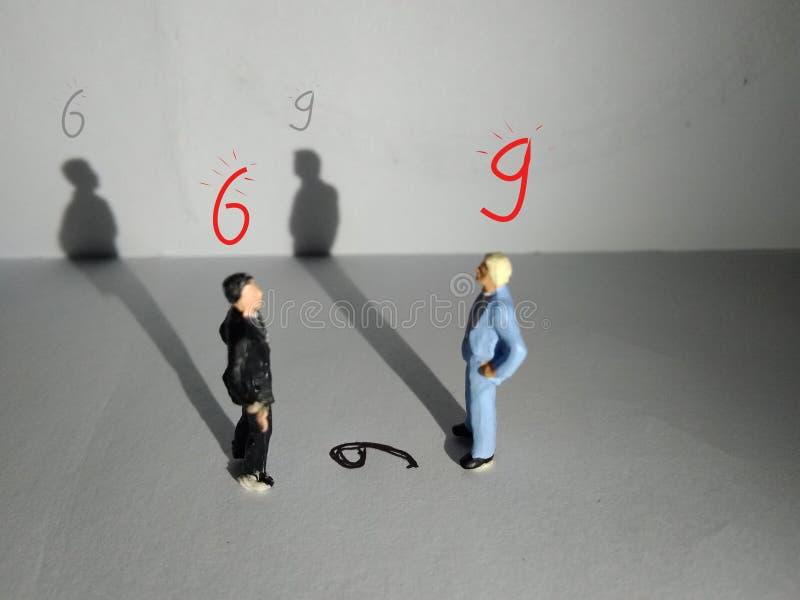 El ejemplo, perspectiva distinta hace otro valor, la mini figura del hombre de negocios derecho juega hacer frente al número seis imagenes de archivo