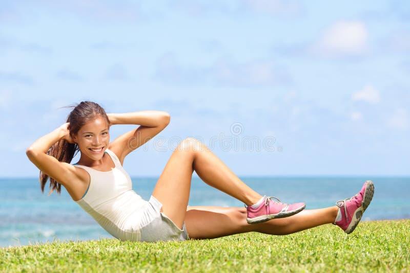 El ejercicio de la mujer de la aptitud que el hacer se sienta sube afuera fotografía de archivo