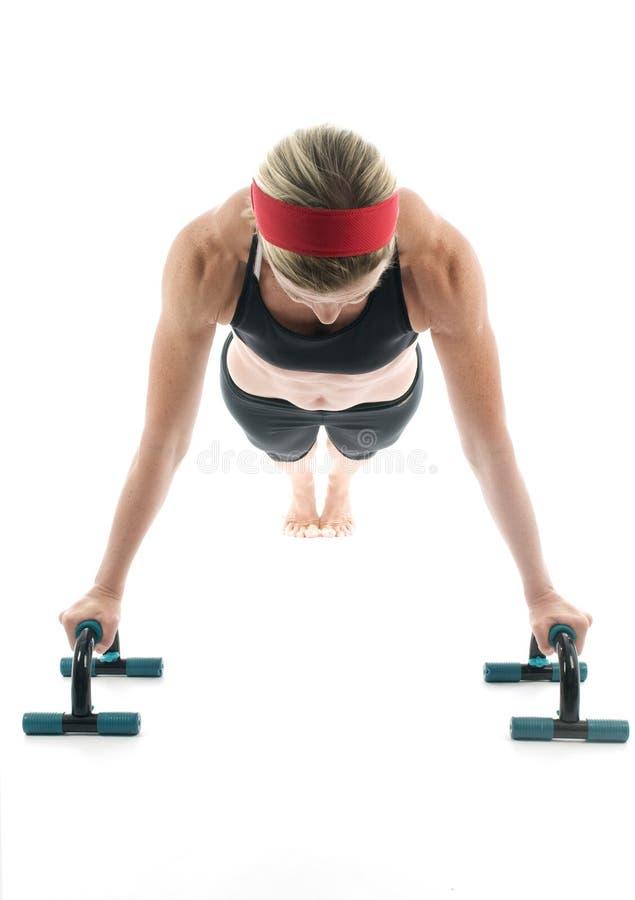 El ejercicio de la mujer empuja hacia arriba la barra de la aptitud foto de archivo
