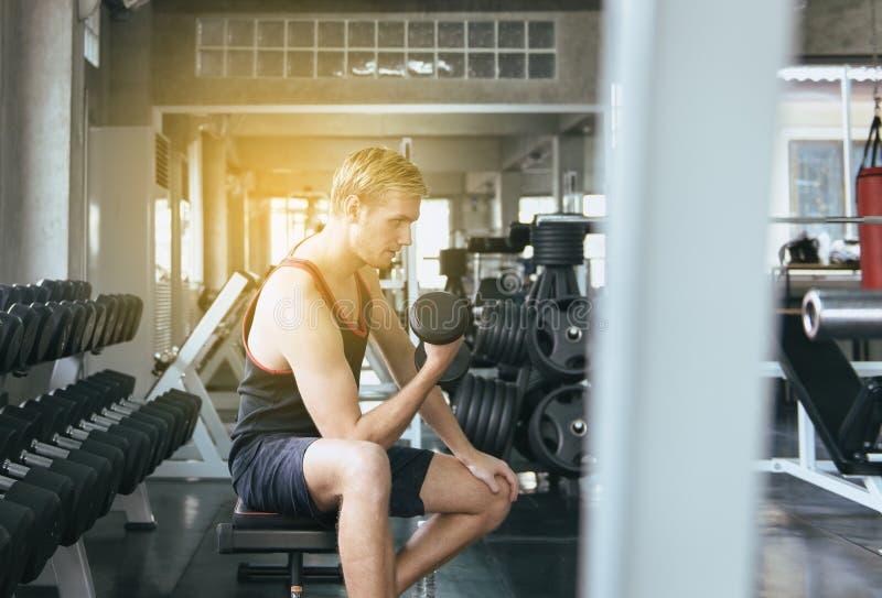 El ejercicio deportivo con pesas de gimnasia, varón del hombre en ropa de deportes hace los ejercicios en el gimnasio imagen de archivo
