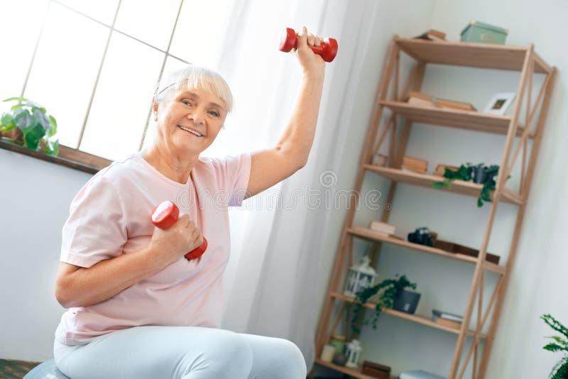 El ejercicio mayor de la mujer en casa que se sienta en bola del ejercicio levanta para arriba pesas de gimnasia imágenes de archivo libres de regalías