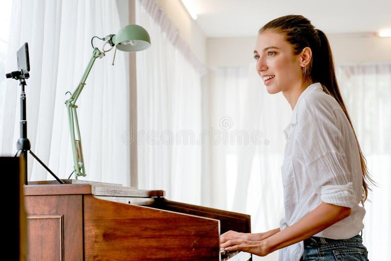 El electone hermoso del juego de la muchacha en sitio y vive en medios sociales y también canta la canción con la emoción feliz imagen de archivo