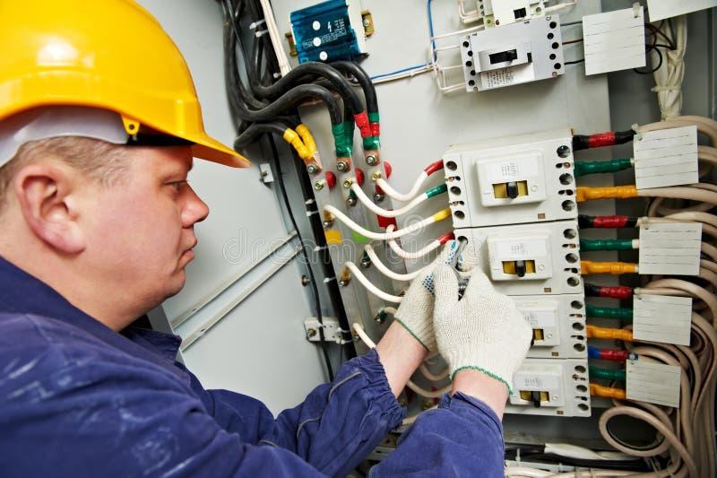 El electricista aprieta los tornillos con la llave inglesa fotos de archivo libres de regalías