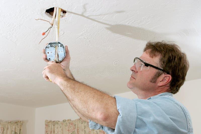 El electricista ata con alambre el rectángulo del techo foto de archivo