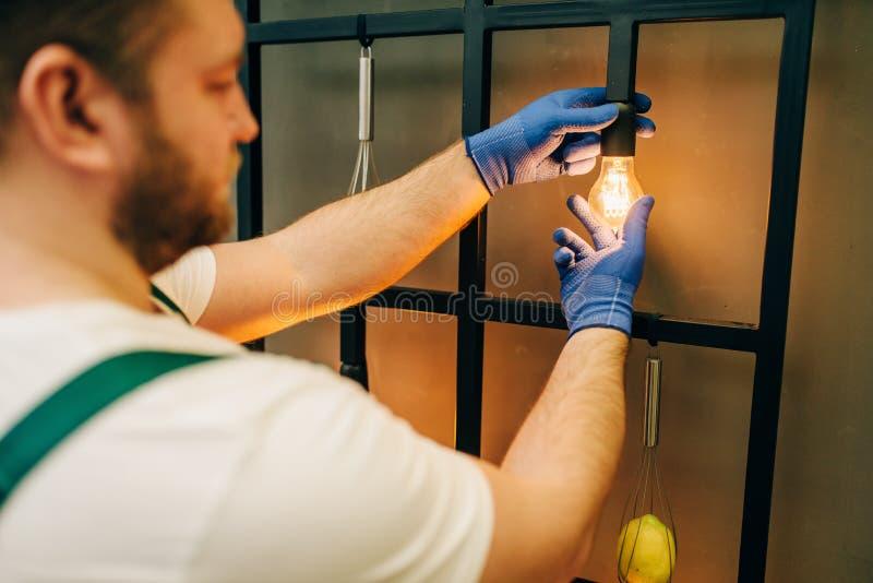 El electricista cambia la bombilla, manitas imagen de archivo