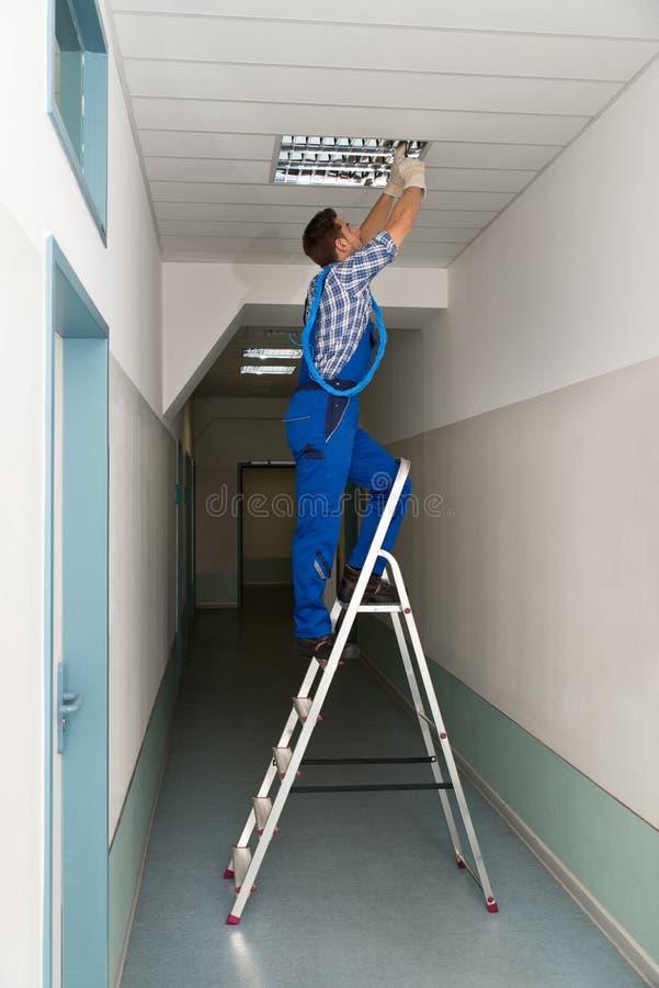 El electricista en la escalera de mano instala la iluminación al techo fotografía de archivo libre de regalías