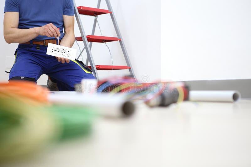 El electricista en el trabajo con destornillador a disposici?n conecta los cables con el z?calo para el cableado el?ctrico fotografía de archivo