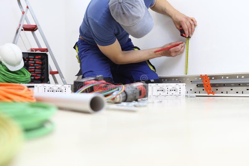 El electricista en el trabajo con medidas del l?piz y del metro en la pared la posici?n para el z?calo el?ctrico, instala los cir foto de archivo libre de regalías