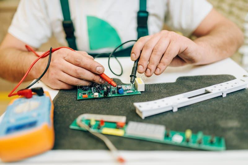 El electricista en uniforme comprueba el microprocesador, manitas imágenes de archivo libres de regalías
