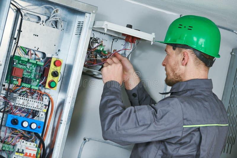 El electricista hace mantenimiento en la sala de máquinas del elevador imágenes de archivo libres de regalías