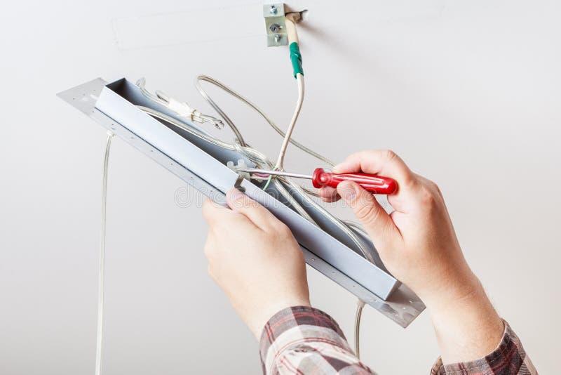 El electricista instala el cableado en lámpara del techo imagenes de archivo