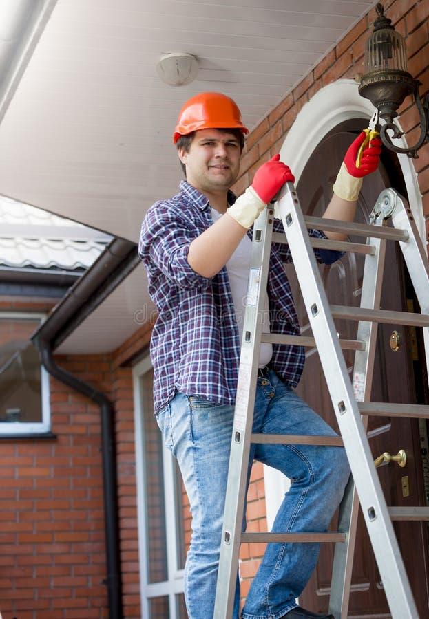 El electricista joven en los guantes de goma y el casco protector que reparan la casa se enciende imágenes de archivo libres de regalías
