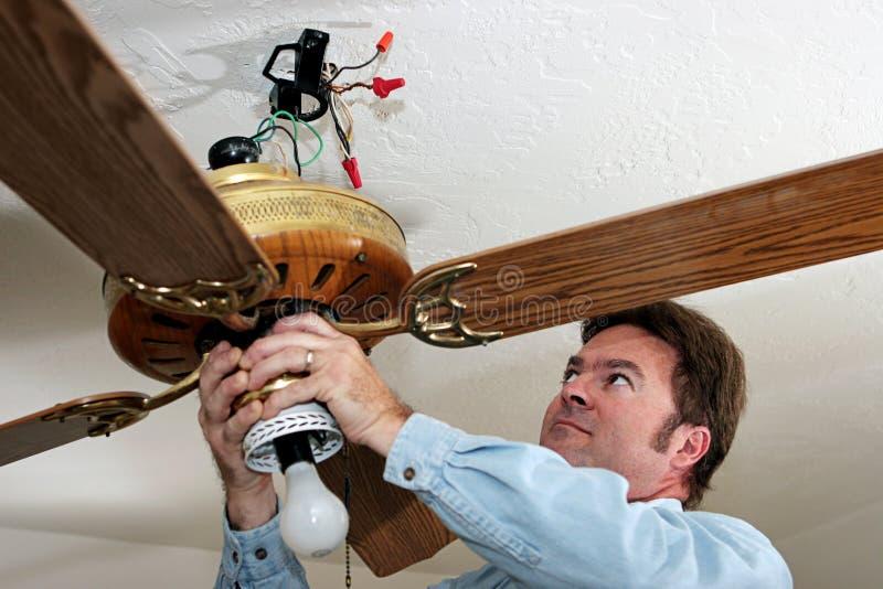 El electricista quita el ventilador de techo imagenes de archivo