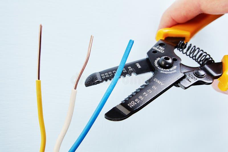 El electricista utiliza el cortador del pelacables durante el cableado eléctrico s foto de archivo