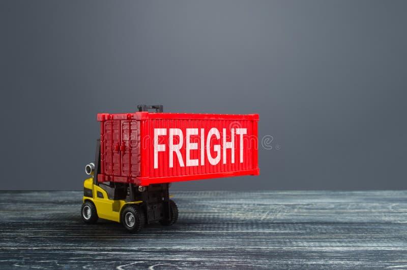 El elevador de horquilla amarillo lleva un contenedor de carga rojo Infraestructura logística de transporte, importación y export foto de archivo