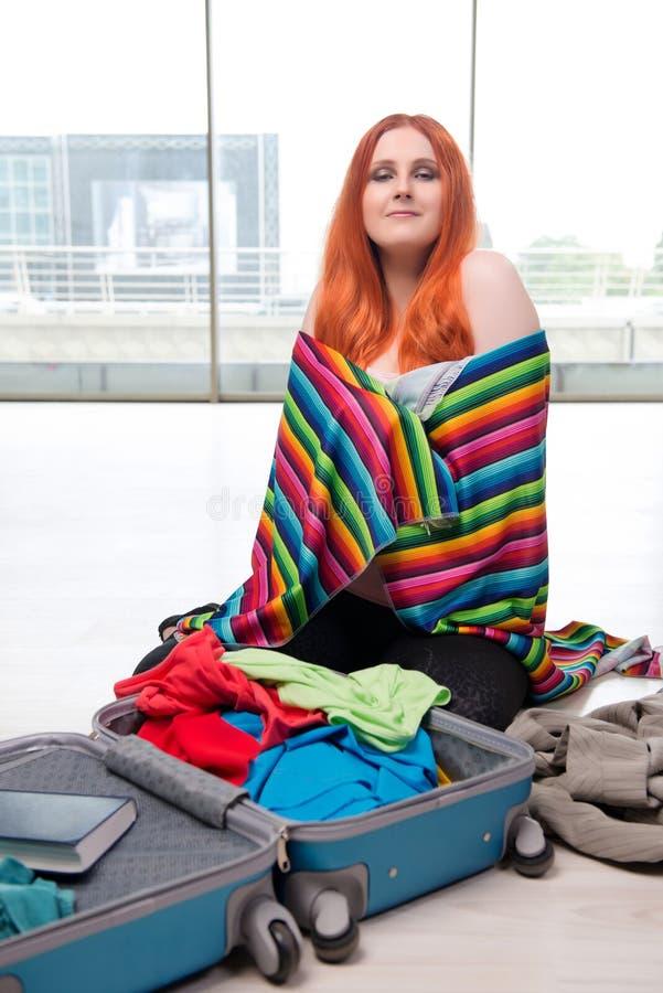 El embalaje de la mujer joven para las vacaciones del viaje imagen de archivo