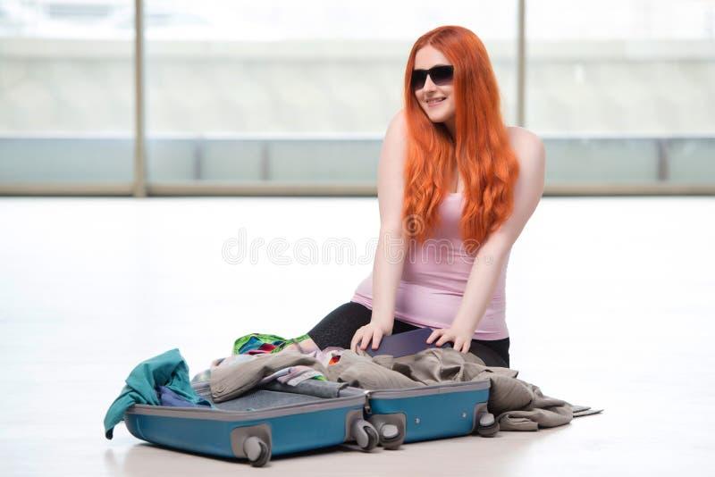 El embalaje de la mujer joven para las vacaciones del viaje foto de archivo libre de regalías