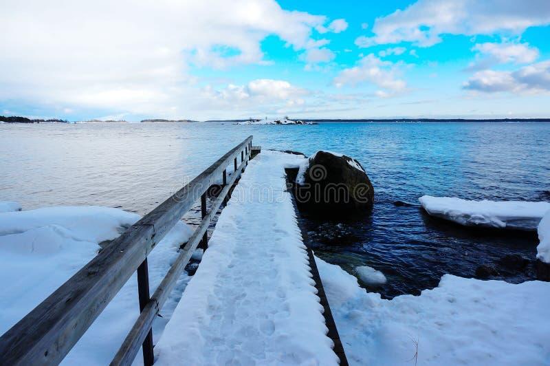 El embarcadero cubierto con nieve y flozen la fusión del mar imagenes de archivo