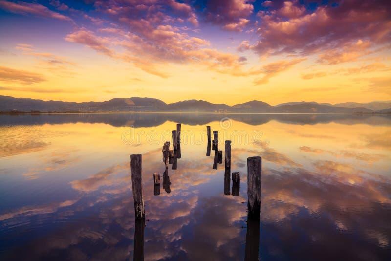 El embarcadero o el embarcadero de madera permanece en un refle caliente de la puesta del sol y del cielo del lago fotos de archivo libres de regalías
