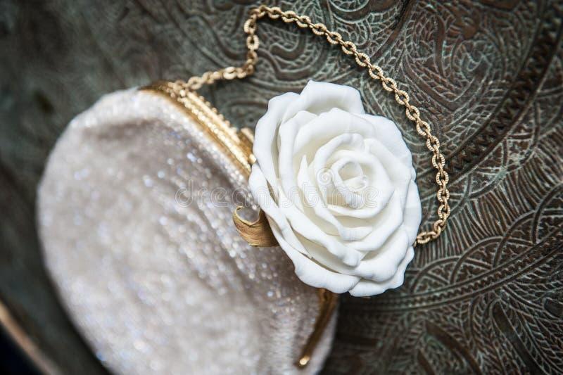 El embrague de las mujeres con la rosa del blanco en la bandeja de cobre amarillo con un ornamento fotos de archivo