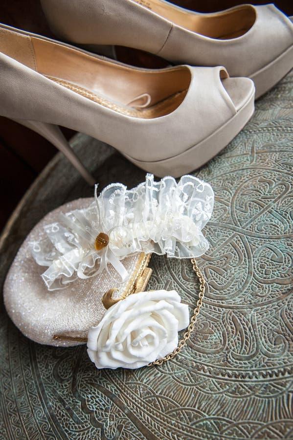 El embrague de las mujeres con la rosa, los zapatos y la liga del blanco en la bandeja de cobre amarillo con un ornamento foto de archivo libre de regalías