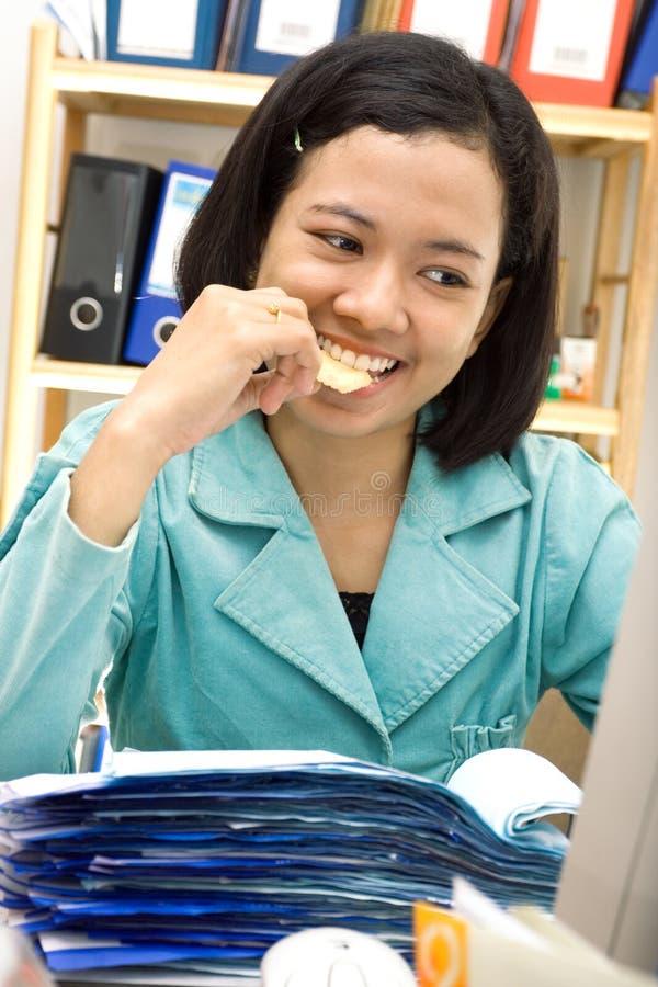 El empleado come el bocado en el trabajo imágenes de archivo libres de regalías