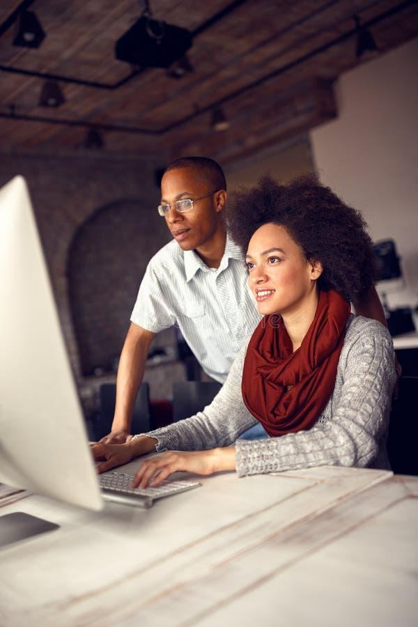 El empleado de sexo femenino consulta con el encargado sobre proyecto foto de archivo