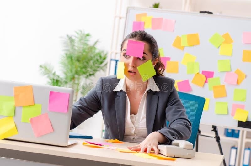 El empleado de sexo femenino joven en concepto de las prioridades que está en conflicto imagen de archivo