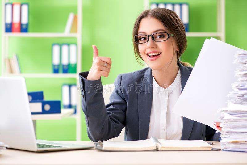 El empleado de sexo femenino joven muy ocupado con papeleo en curso imagen de archivo